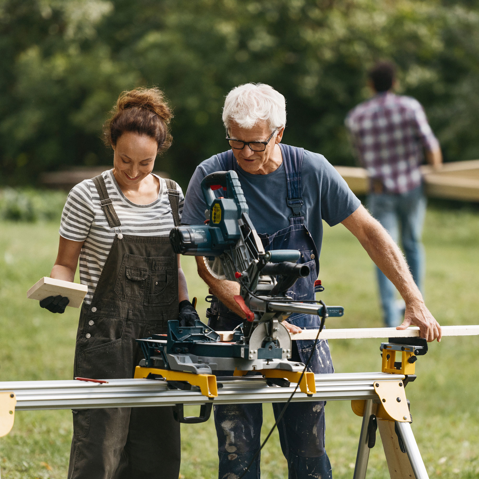 Woman and man sawing planks